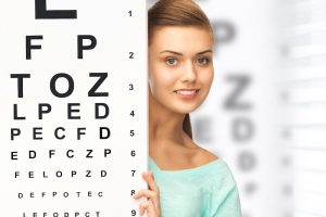 Girl behind a large eye chart