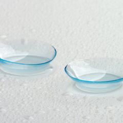 Two Contact Lenses with Water Droplets isolated on Grey Wet background