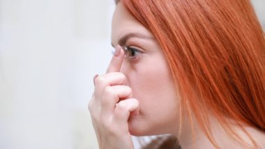 Girl with red hair inserting a contact lens into her eye