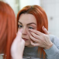 Girl inserting a contact lens in the mirror